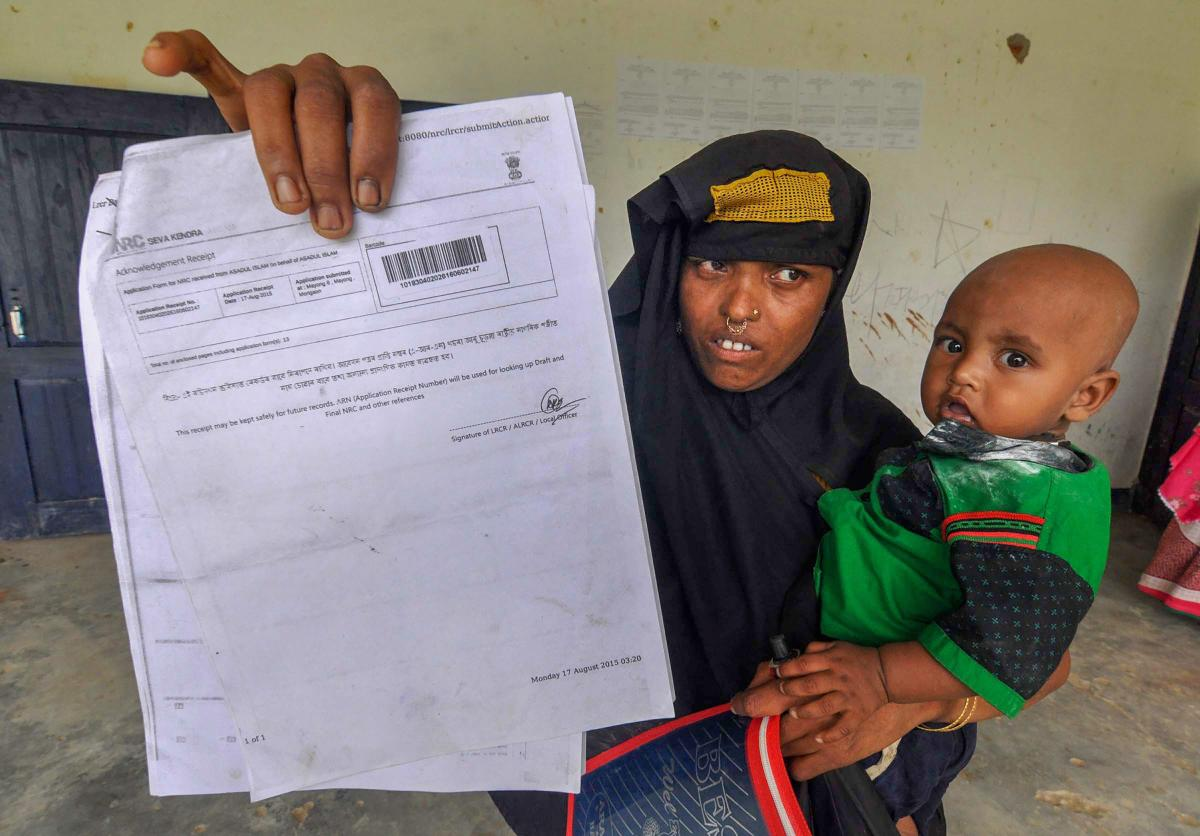 A woman shows an acknowledgment receipt to check her name in the final draft of Assam's National Register of Citizens at an NRC Seva Kendra in Morigaon. PTI