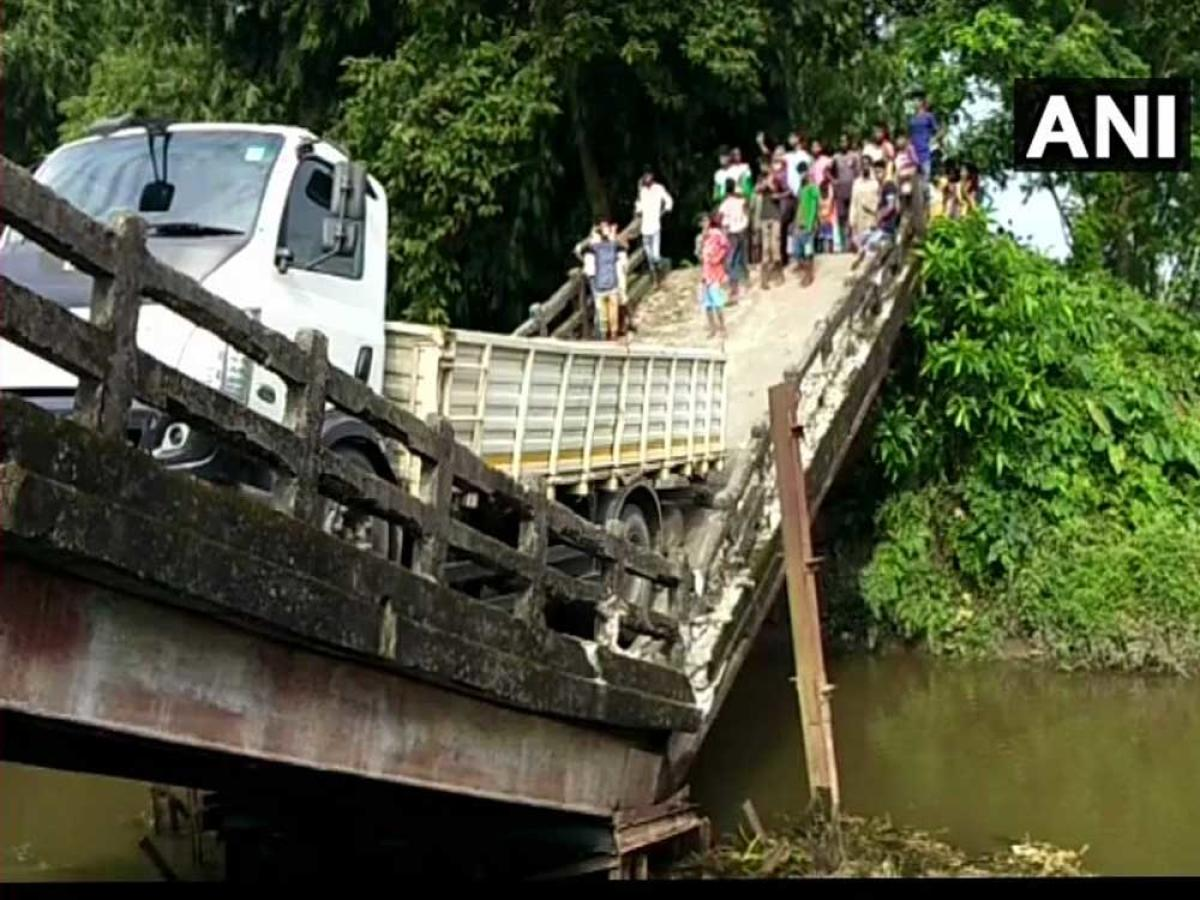 The truck, which was crossing the bridge, is still hanging from the broken portion of the structure that connects Manganj area to Siliguri, a major city in north Bengal. (Image courtesy ANI/Twitter)