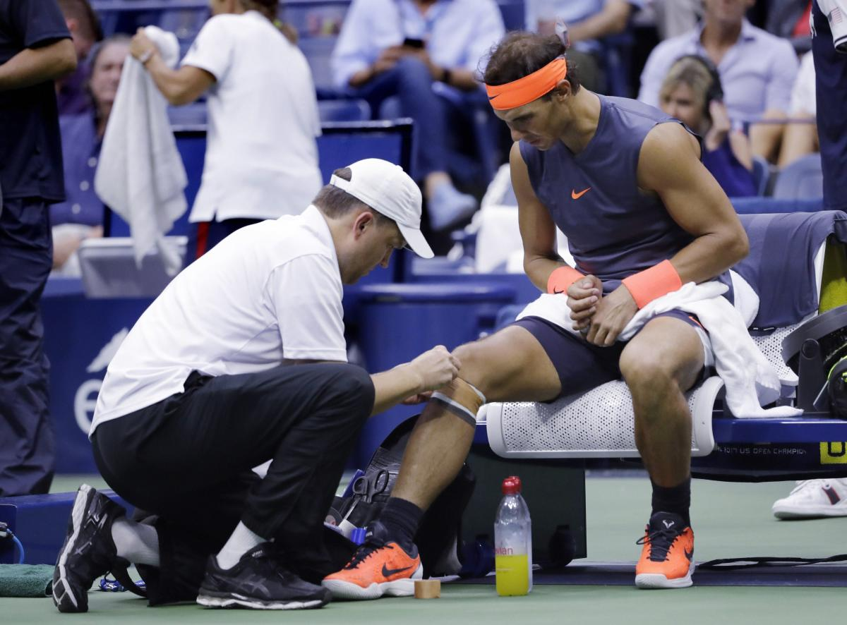 Spain's Rafael Nadal is treated by a trainer during a change over against Juan Martin del Potro in the men's semifinal. AP/PTI