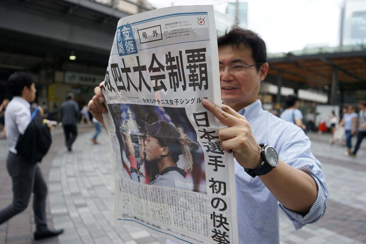 GROUND BREAKING A pedestrian reads an extra edition of a Japanese newspaper which has the report of Naomi Osaka's triumph over Serena Williams in the US Open final. AFP
