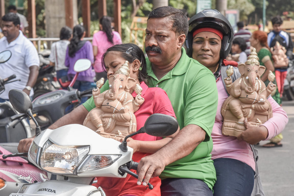 People take home clay Ganesha idols that were distributed by Mayor R Sampath Raj at an awareness programme in Cubbon Park on Sunday. DH Photo/S K Dinesh
