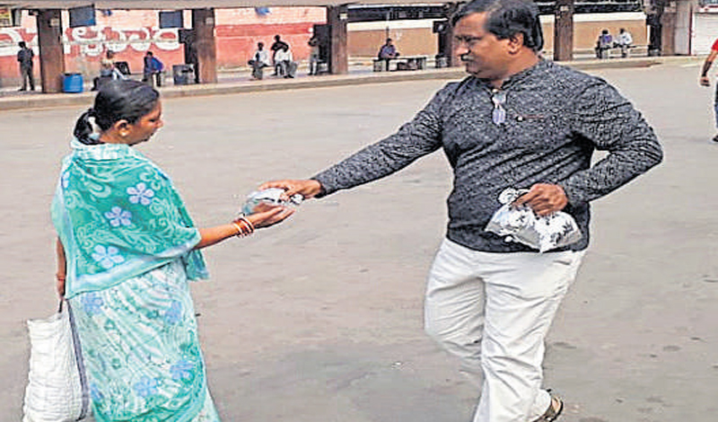A citizen distributes food packets to stranded passengers in the Kempegowda bus station.