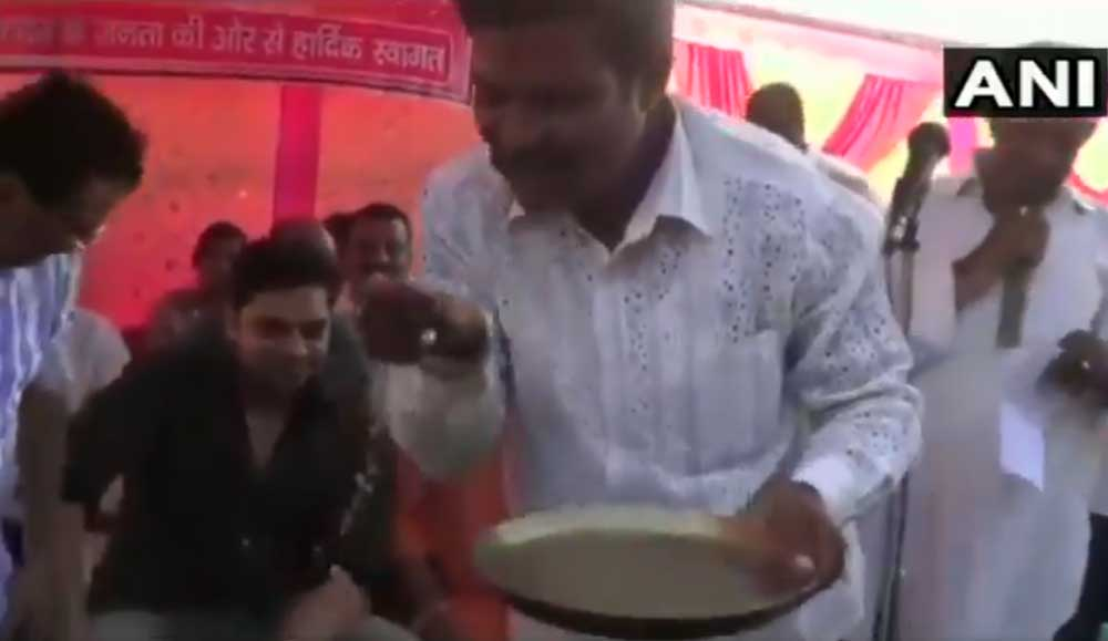BJP supporter drinking water after washing the feet of BJP MP Nishikant Dubey. Picture courtesy ANI