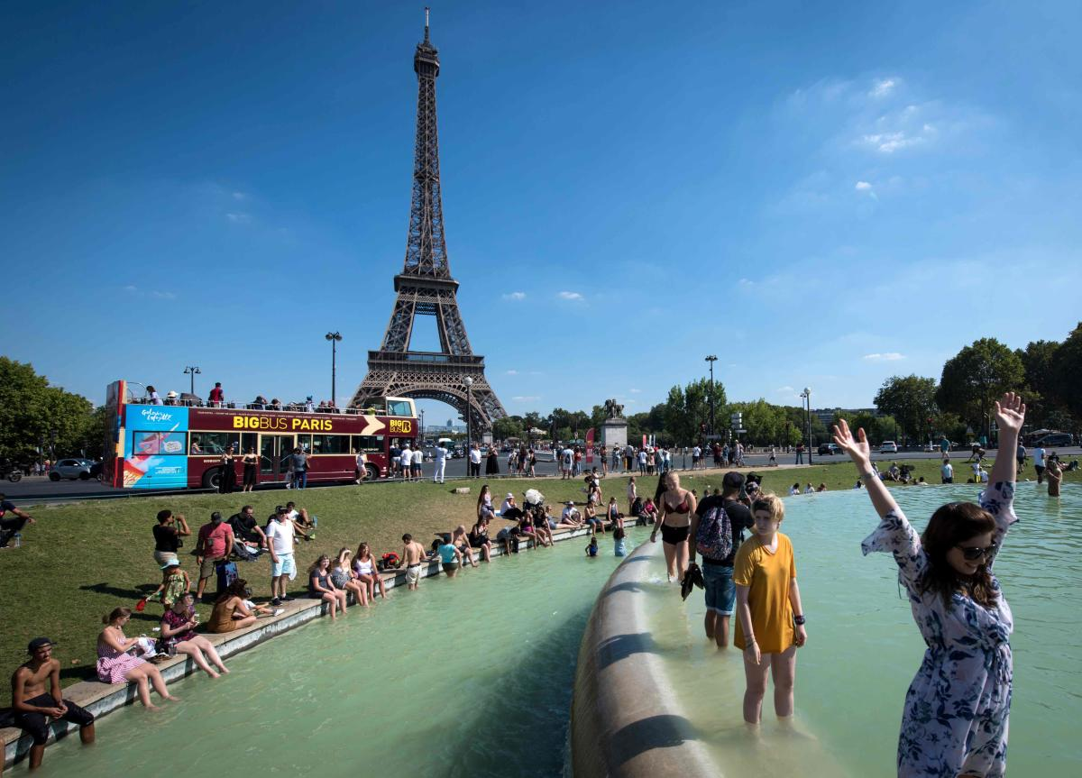 People cool themselves at the Trocadero Fountain in front of The Eiffel Tower in Paris on August 2, 2018, as a heatwave continues across Europe. / AFP PHOTO / GERARD JULIEN