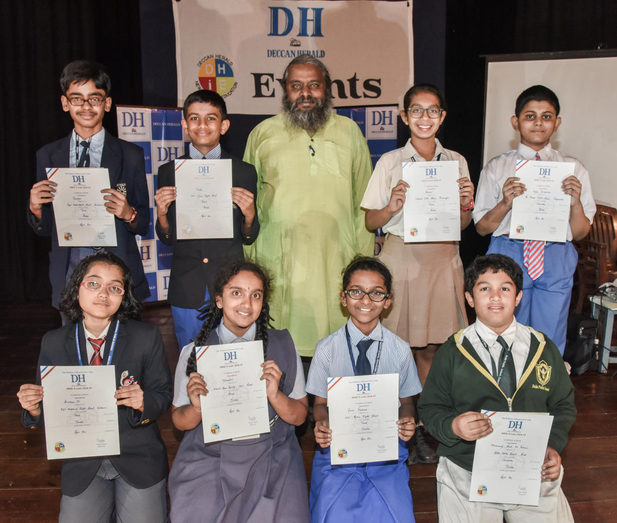 Senior category (standing from Left) Preetham R, Ryan International School (First), Chandan U Hande, HAL Gnanajyothi (Second), Sharvari P B, National Public School Koramangala (Third) and Arjun Ravisankar, St Thomas Public School (Consolation). Junior category(sitting from left) Anushree Maitra, BGS National Public School (First), Mrinalini, Mahila Seva Samaj (Second), Gauri Pradeesh (Third) and Mohammed Saad ur Rahman, DPS South (Consolation) with Prof Arul Mani (centre). (DH Photo/S K Dinesh)