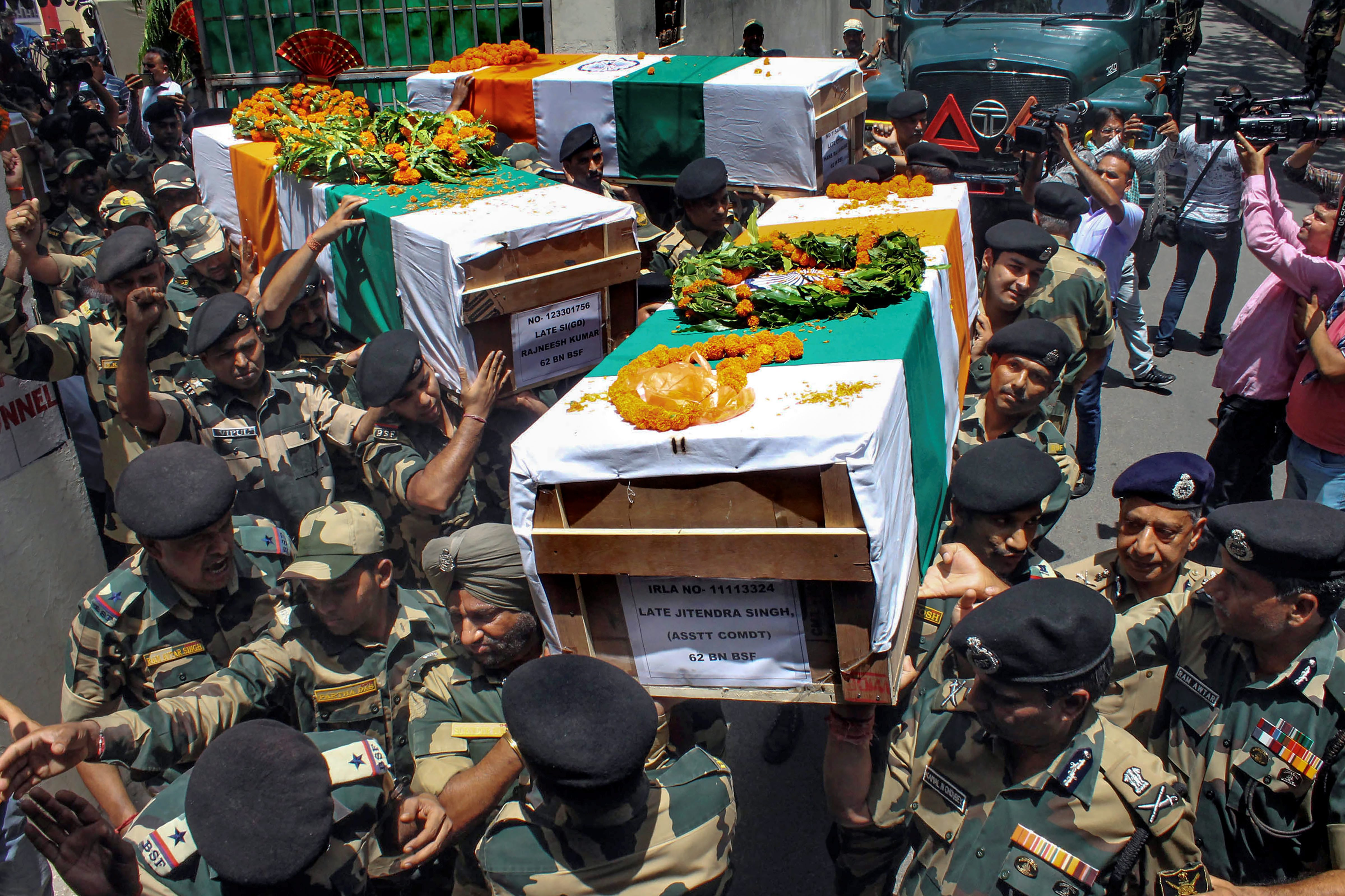BSF officials and jawans carry the bodies of four BSF personnel, killed in Pakistani firing, after a wreath laying ceremony at Paloura BSF Headquarters in Jammu on Wednesday. PTI