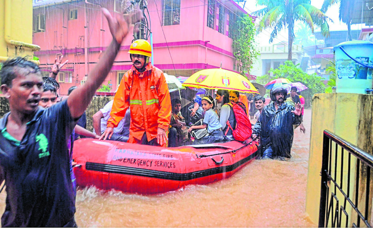 Rescuers shift schoolchildren to a safer place from a flooded locality, after a thunderstorm in Mangaluru on Tuesday. PTI