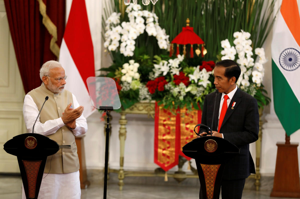 Indian Prime Minister Narendra Modi applauds Indonesia President Joko Widodo after he made an address following their meeting at the presidential palace in Jakarta, Indonesia on Wednesday. (REUTERS/Darren Whiteside)