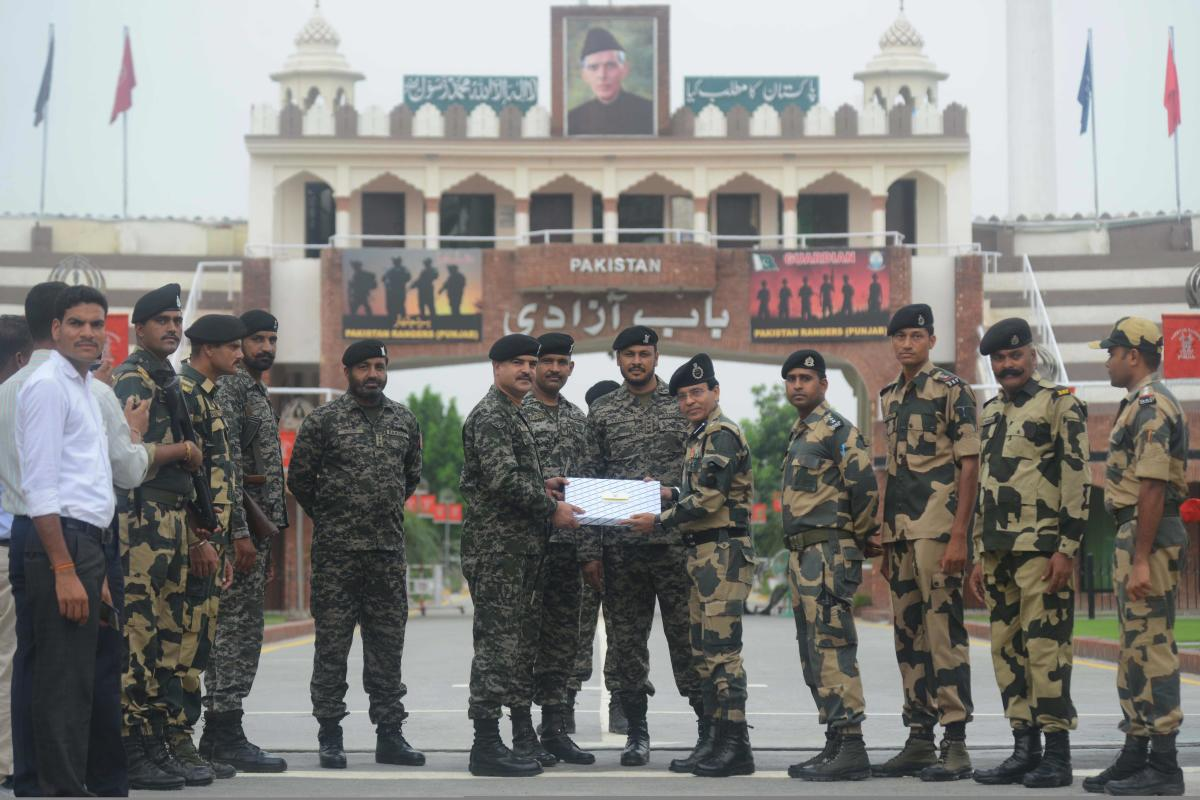 Pakistani Wing Commander Bilal (6L) presents sweets to Indian Border Security Force (BSF) Commandant Sudeep (5R) on the occasion of Eid al-Adha at the India-Pakistan Wagah border post on August 22, 2018. - AFP