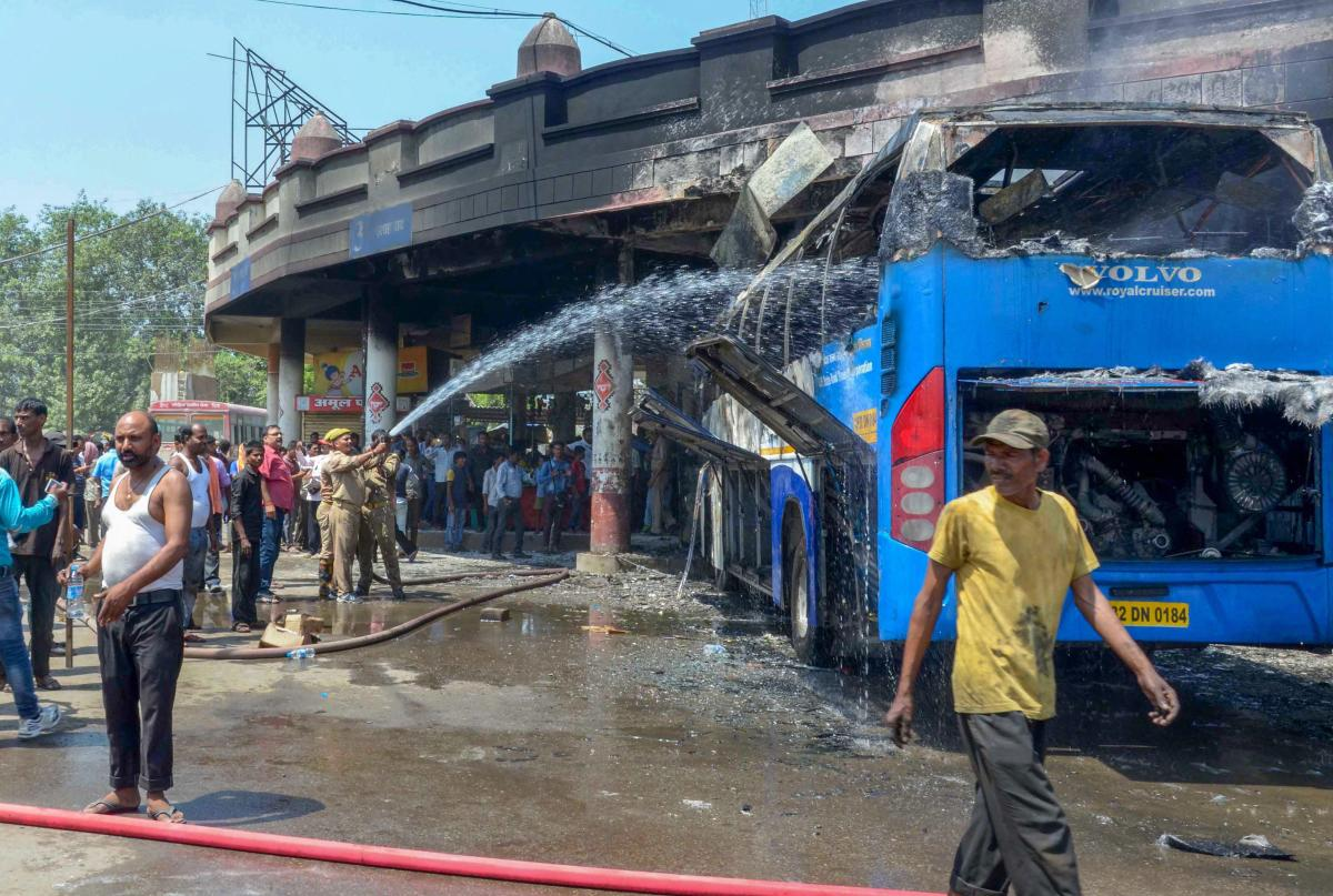 Firefighters douse a fire at a roadways bus that was reportedly torched by a woman protester during a protest for the separate state of 'Purvanchal', in Varanasi on Wednesday. PTI