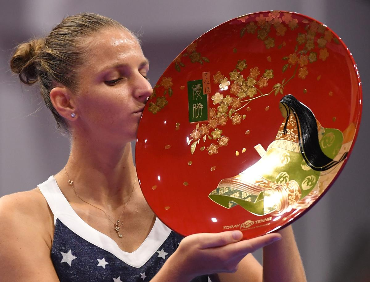TOO GOOD Karolina Pliskova of the Czech Republic kisses the winner's trophy after beating Japan's Naomi Osaka in the final of the Pan Pacific Open in Tokyo on Sunday. AFP