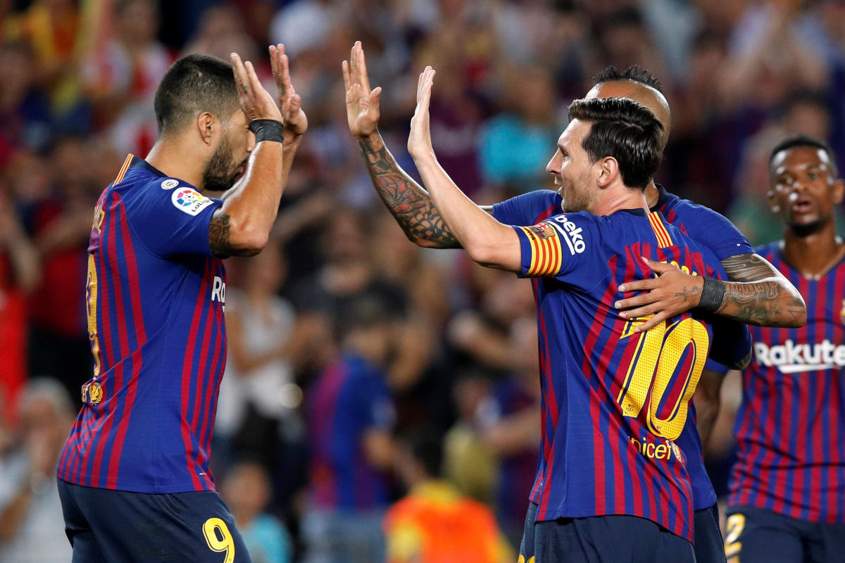 Barcelona's Lionel Messi celebrates with team-mates Luis Suarez (left) and Arturo Vidal after scoring against Girona on Sunday. REUTERS