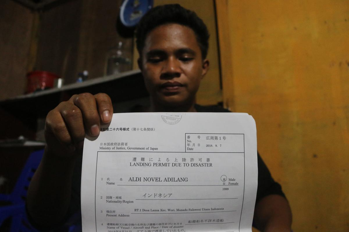 This picture taken in Wori, North Minahasa, Sulawesi on September 16, 2018 shows Indonesian teenager Aldi Novel Adilang showing a letter of landing permit due to disaster in Wori. AFP