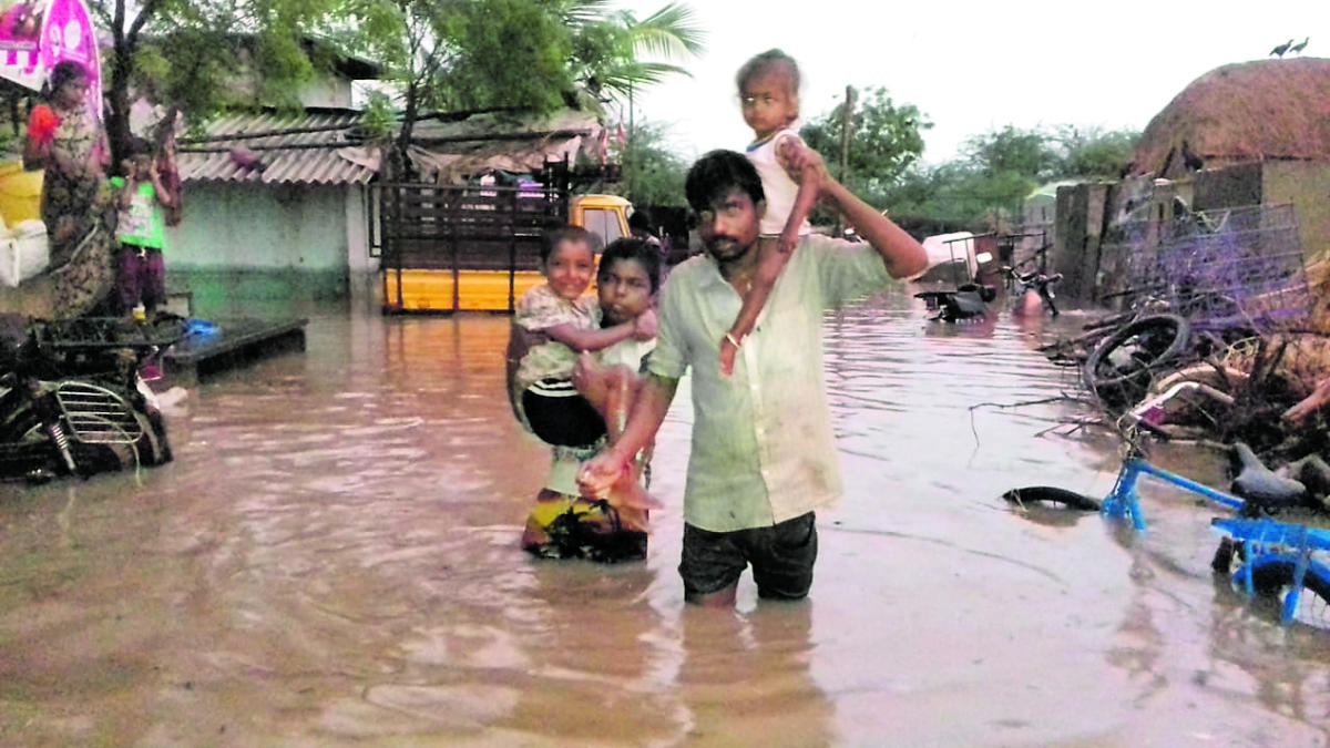 A man carries his children to safety on a waterlogged street at Handihal village in Ballari taluk on Monday. DH Photo
