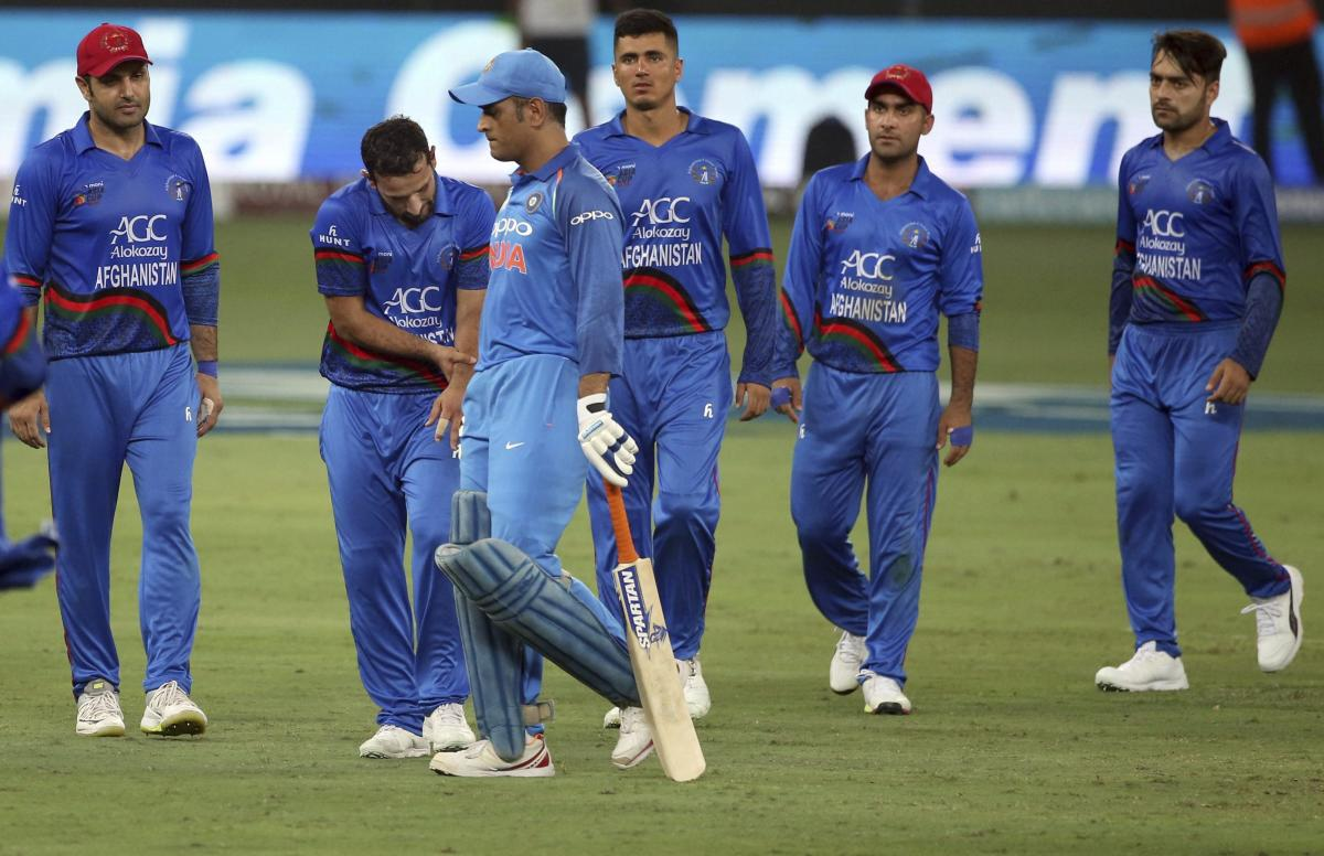 Dubai: India's Mahendra Singh Dhoni, third left, leaves the field after losing his wicket as Afghanistan's Javed Ahmadi, second left, holds his wrist after he was hit by the ball during the one day international cricket match of Asia Cup between India and