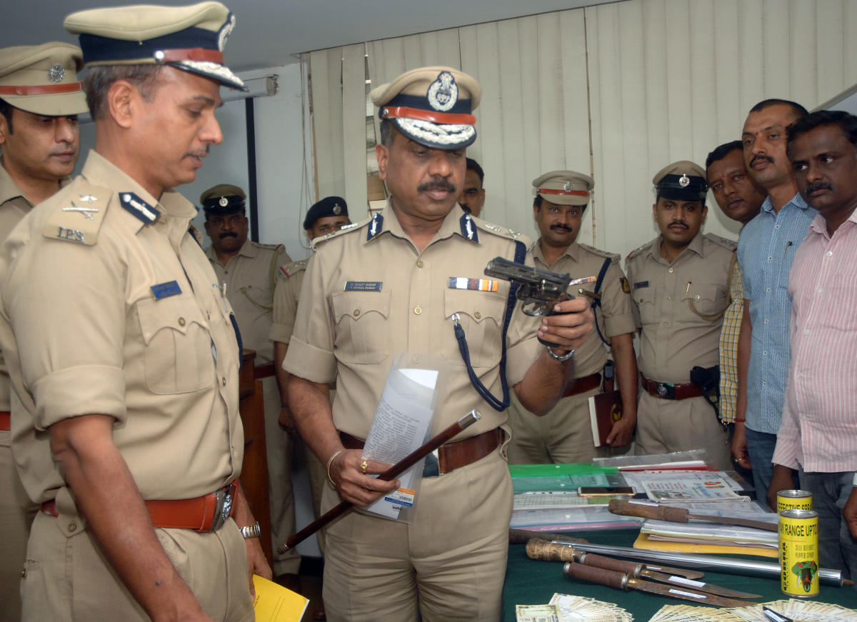Police Commissioner T Suneel Kumar and Additional Commissioner of Police (Crime) Alok Kumar look at pistols, knife and property documents seized from rowdies houses in the city on Thursday.