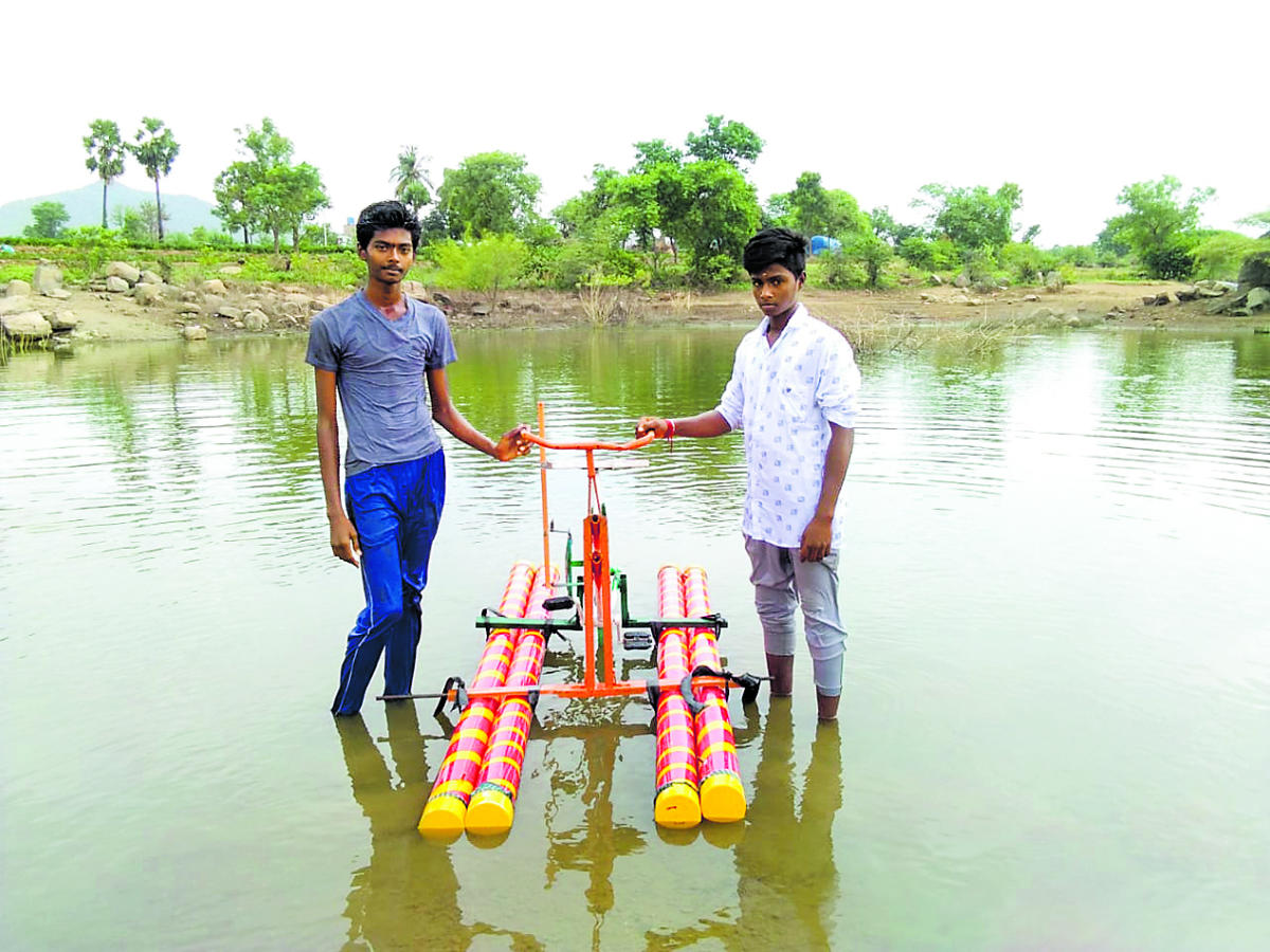 Polytechnic students Tamil Kumaran and Guna seen with their invention, a bicycle that moves on water.