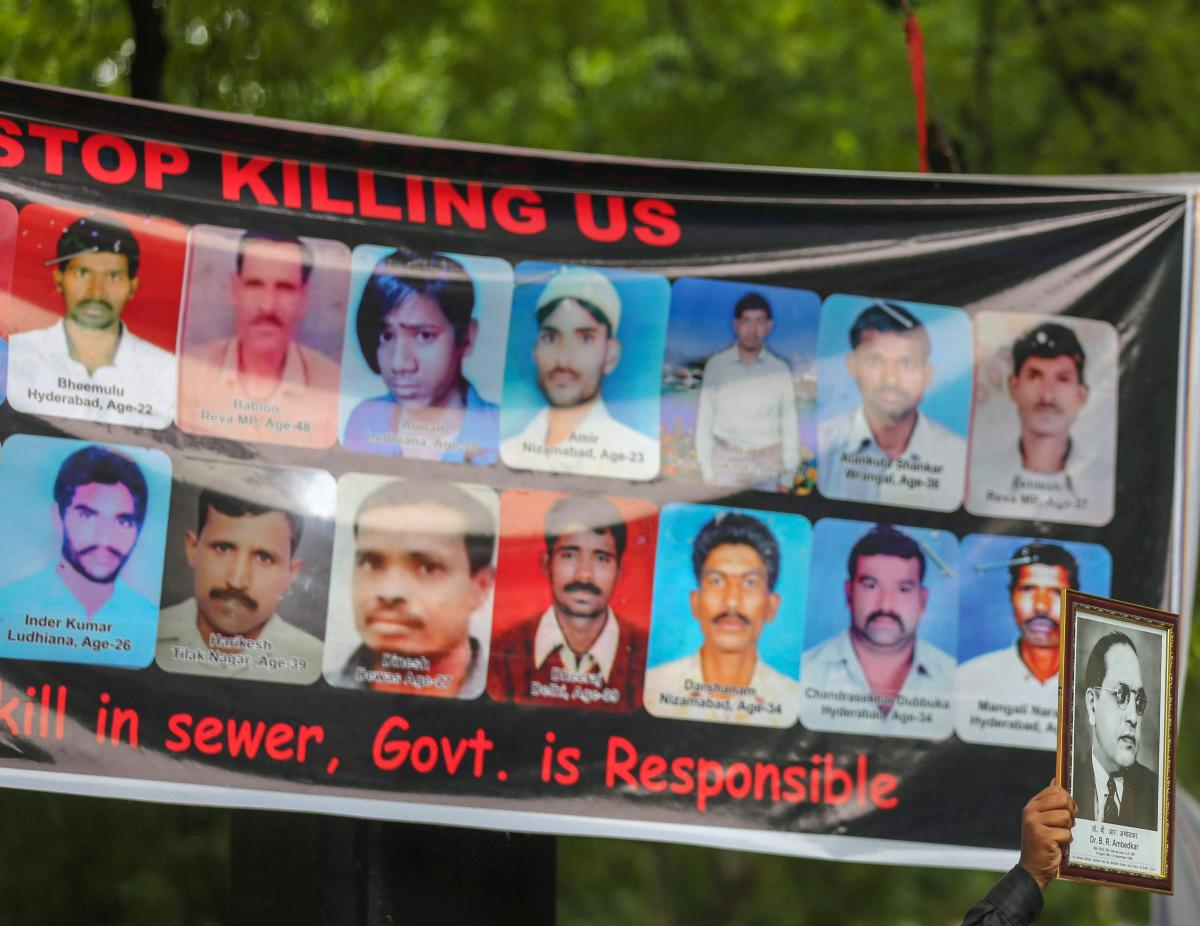 A protestor displays a photo of BR Ambedkar in front-of a banner displaying photos of manual scavengers who lost their lives, during a protest against the violation of Manual Scavenging Prohibition Act 2013, at Jantar Mantar in New Delhi. (PTI Photo)