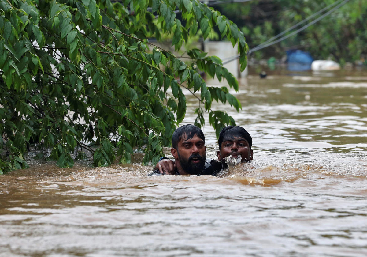 A man rescues a drowning man from a flooded area after the opening of Idamalayr, Cheruthoni and Mullaperiyar dam shutters following heavy rains, on the outskirts of Kochi. Reuters photo