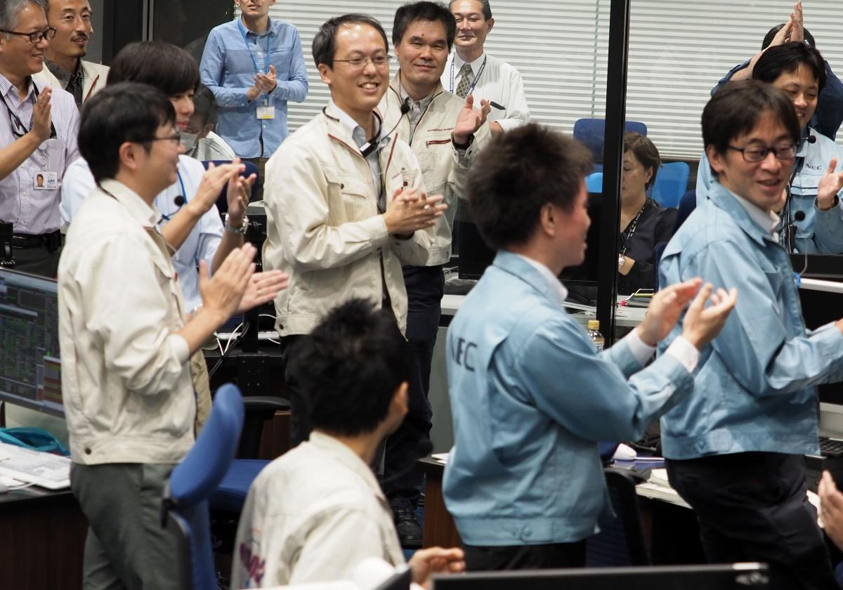 In this handout photograph taken and released by Institute of Space and Astronautical Science (ISAS) of Japan Aerospace Exploration Agency (JAXA) on October 3, 2018, researchers and employees applaud at a control room in Sagamihara, Kanagawa prefecture, d