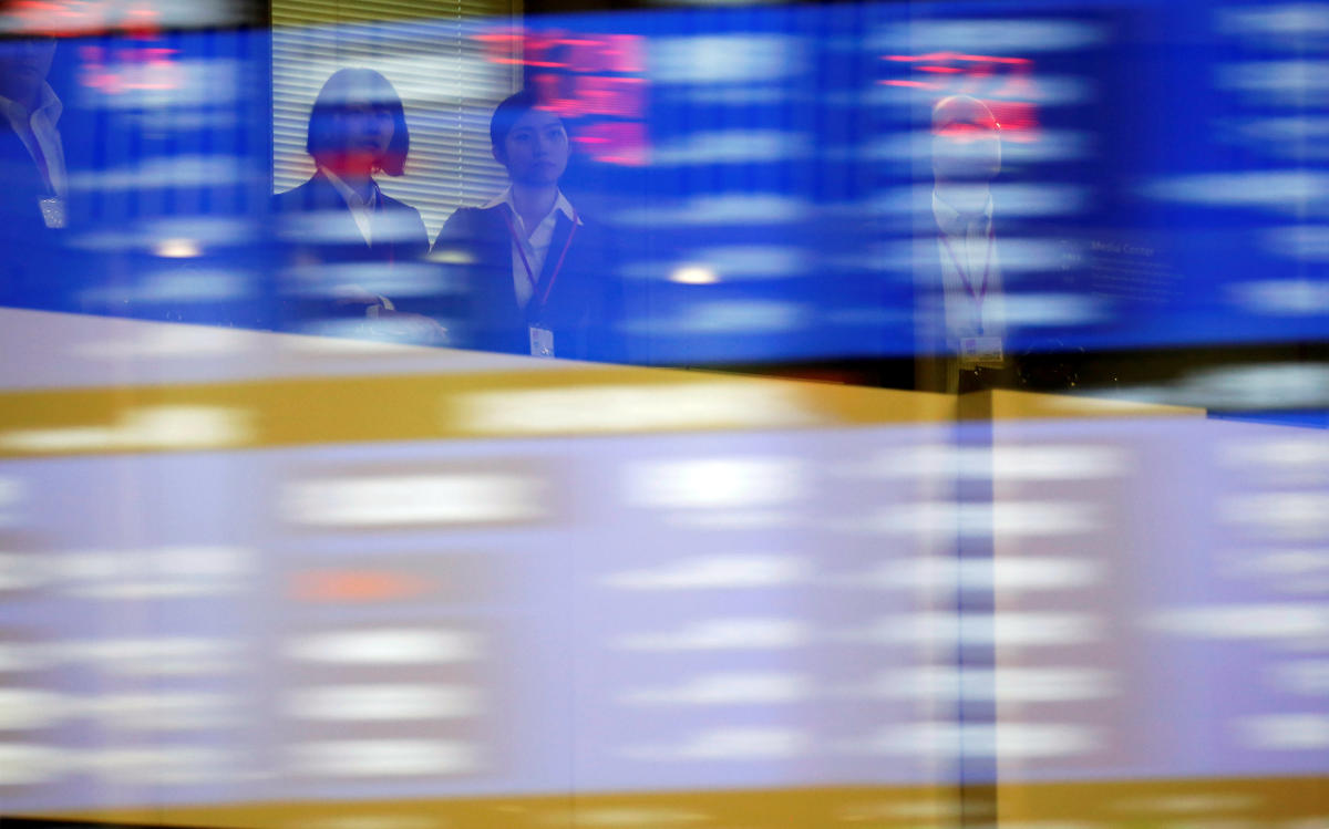 Visitors are seen as market prices are reflected in a glass window at the Tokyo Stock Exchange (TSE) in Tokyo, Japan. (REUTERS File Photo)
