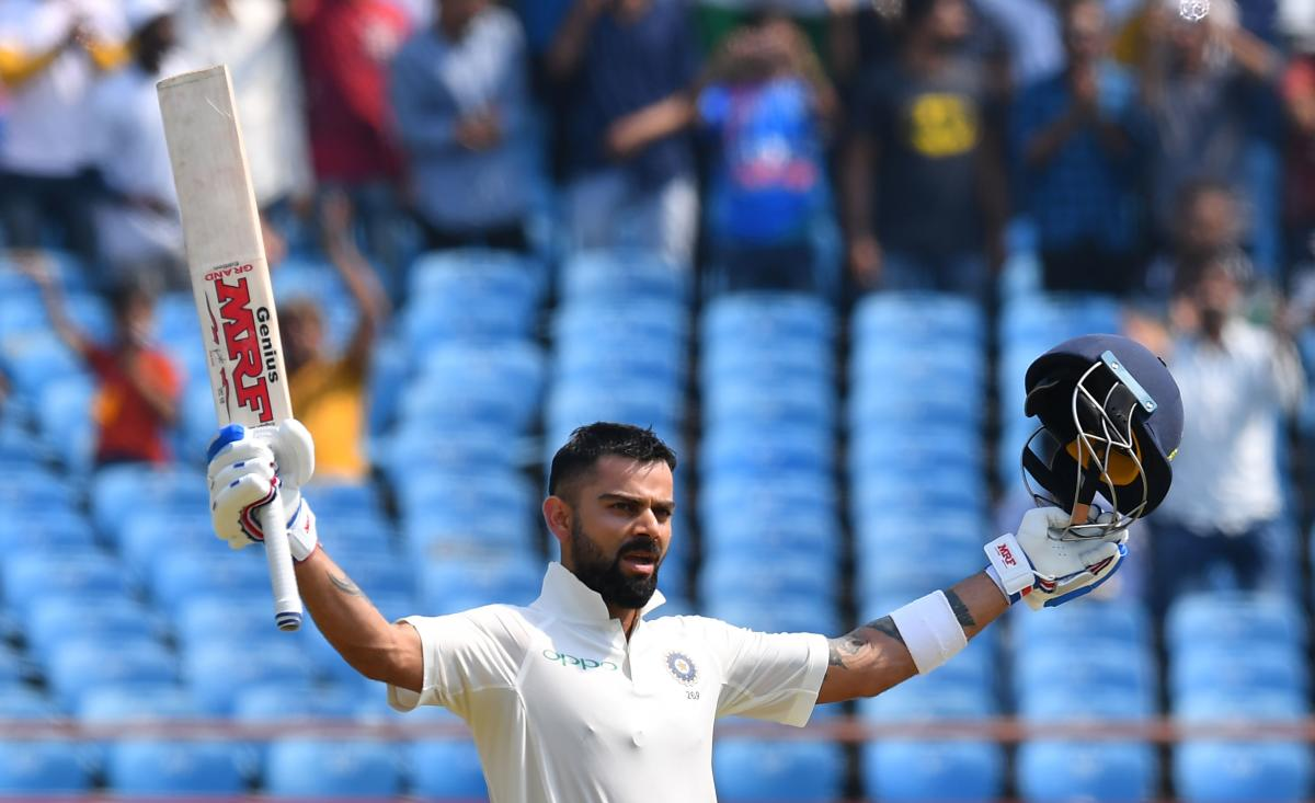 Indian cricket captain Virat Kohli celebrates after reaching his century during the second day's play of the first Test cricket match between India and West Indies at the Saurashtra Cricket Association stadium in Rajkot on October 5, 2018. (AFP Photo)