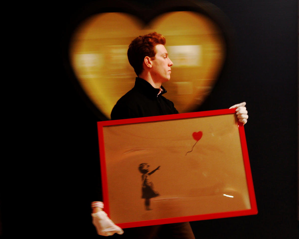 """An employee walks with Banksy's """"Girl and Balloon"""" 2009, at Bonhams auction house in London on March 23, 2012. Reuters"""