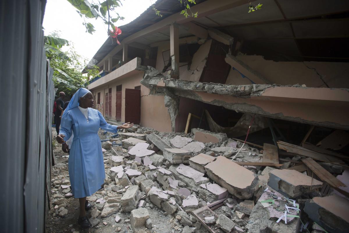 Sr Maryse Alsaint walks alongside a school damaged by a magnitude 5.9 earthquake the night before, in Gros Morne, Haiti on Sunday. (AP/PTI photo)