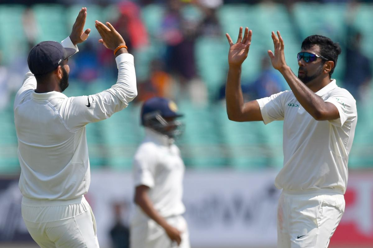 India's Cheteshwar Pujara (L) and Ravichandran Ashwin (R) celebrate after the dismissal of West Indies batsman Keith Brathwaite during the third day's play of the first Test cricket match between India and West Indies at the Saurashtra Cricket Association