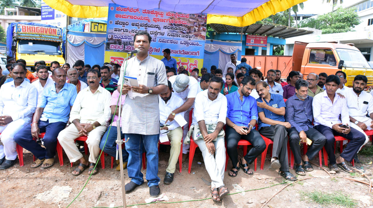 Pumpwell Melsethuve Horata Samithi convener Sunil Kumar Bajal addresses protesters during a protest against the delay in the completion of Pumpwell flyover.