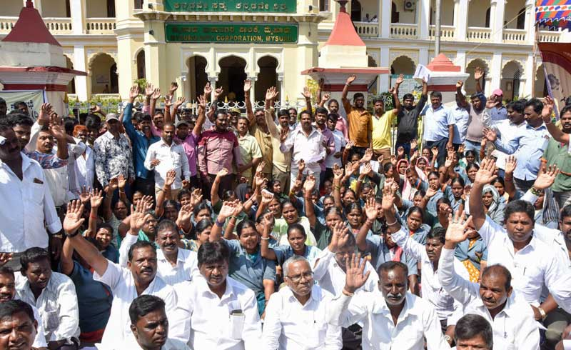 Karnataka Rajya Nagara Palike, Nagarasabhe, Purasabhegala Pourakarmikara Mahasangha members stage protest for various demands in front of Mysuru City Corporation in Mysuru on Wednesday. (DH Photo by Savitha B R)
