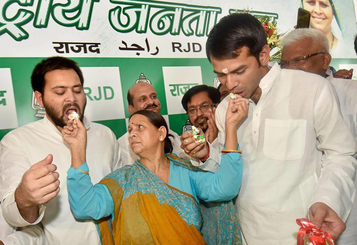 Former Bihar chief minister Rabri Devi shares a cake with her sons Tejaswi Yadav and Tej Pratap while celebrating her husband RJD chief Lalu Prasad 71st birthday in Patna. (PTI File Photo)