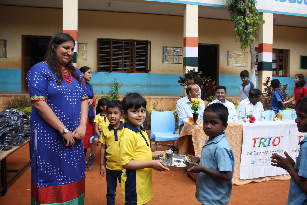A student of Trio World School gives away a stainless steel plate and glass to a student of Government Primary and Upper Middle School in Kodigehalli as part of the Joy of Giving week recently.