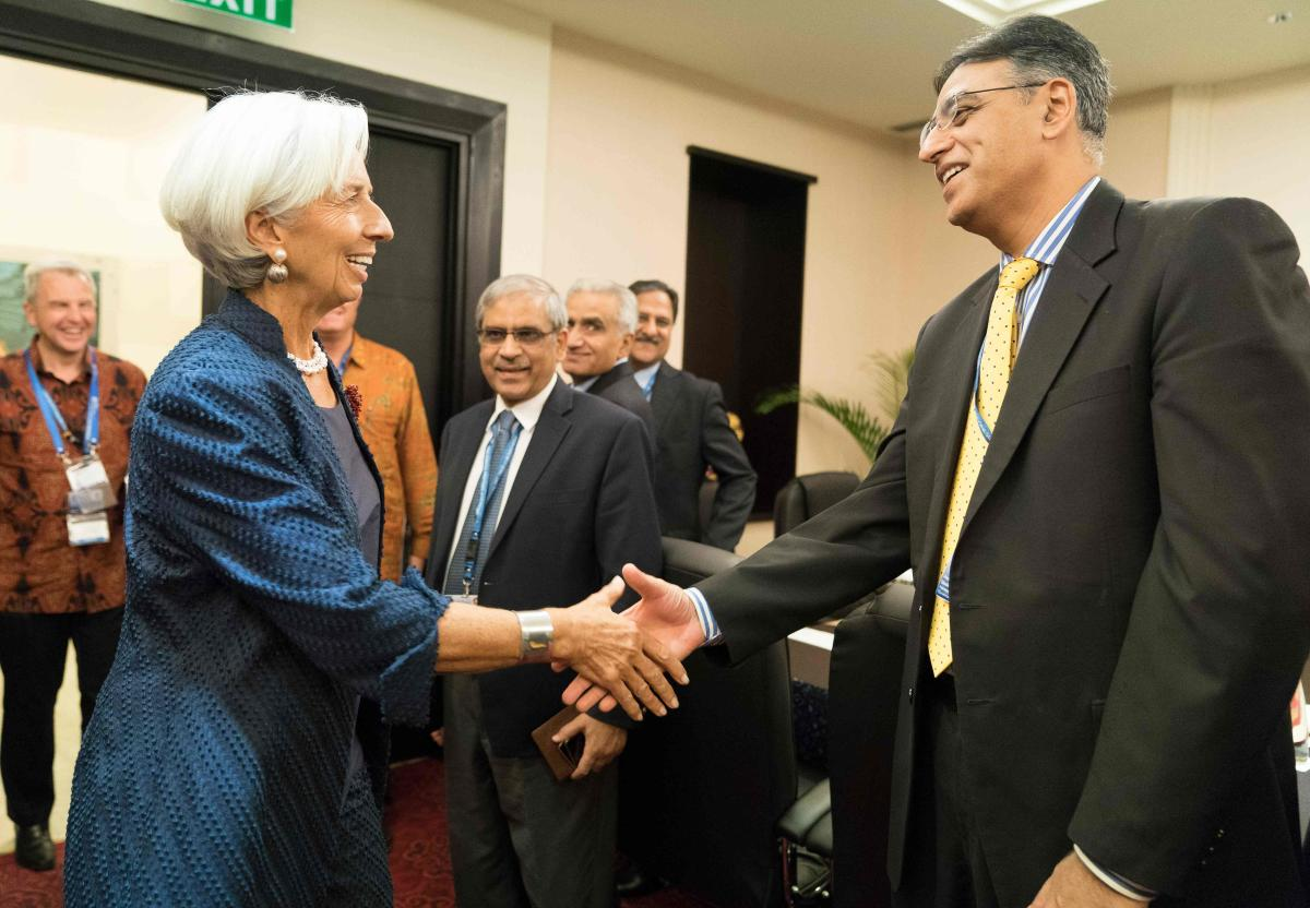 This handout photo taken and released by the International Monetary Fund (IMF) on October 11, 2018 shows IMF Managing Director Christine Lagarde greeting Pakistan Finance Minister Asad Umar at the Bali Convention Centre.