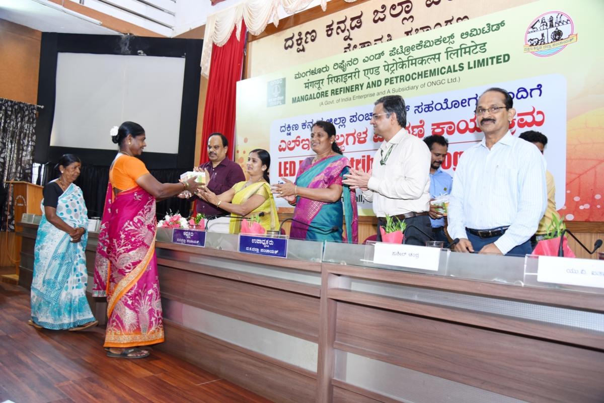 ZP President Meenakshi Shanthigodu distributes LED bulbs to a beneficiary at a programme organised at the Zilla Panchayat Auditorium in Mangaluru on Friday.