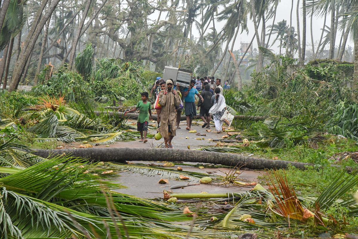 Srikakulam: A group of people relocate to safer places as Cyclone Titli hits Barua village, in Srikakulam, Thursday, Oct 11, 2018. The 'very severe' cyclonic storm 'Titli' left two persons dead besides causing widespread damage in Srikakulam. (PTI Photo)