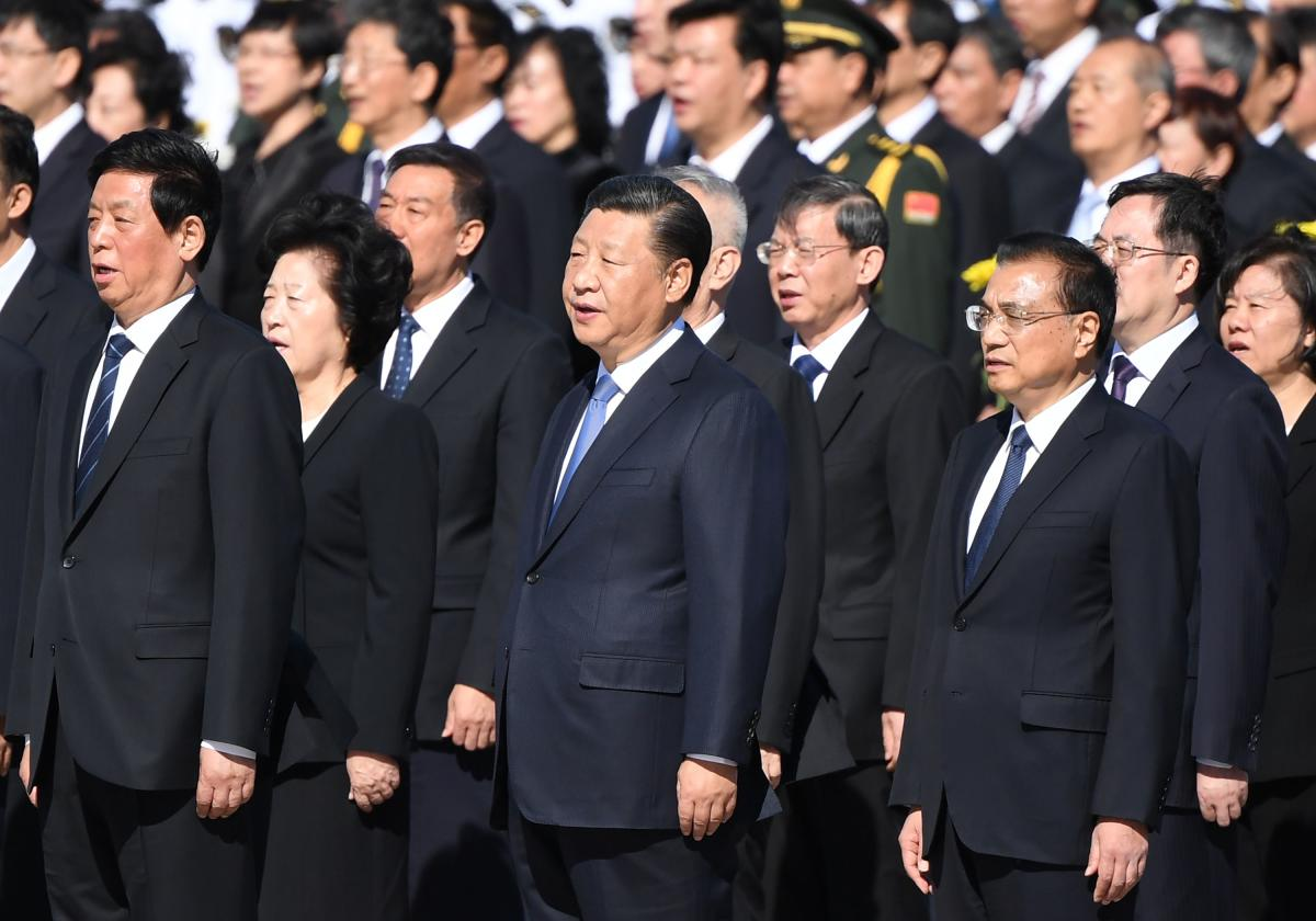 Chinese President Xi Jinping sings the national anthem with National People's Congress leaders during a ceremony in Beijing's Tiananmen Square, on the eve of National Day on September 30, 2018. AFP
