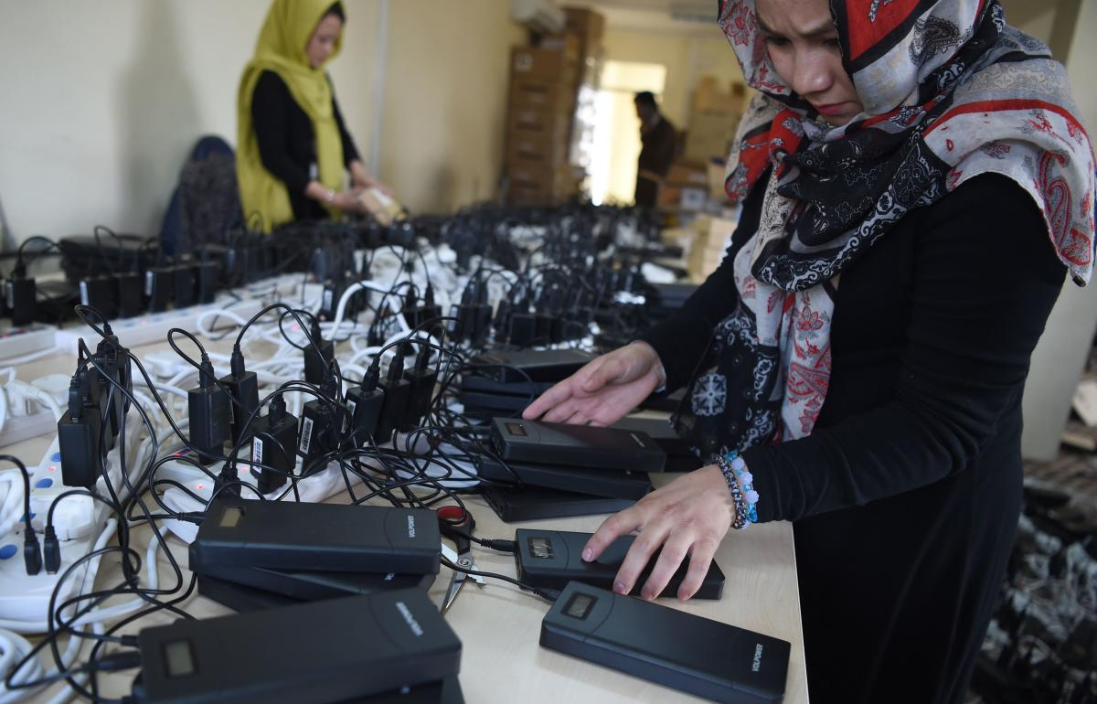 Afghan employees of the Independent Election Commission (IEC) charges power bank devices at a warehouse in Kabul. (AFP file photo)