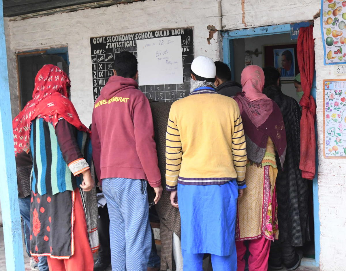 People wait in a queue to cast their vote at a polling station during the fourth phase of municipal elections at Gulab Bagh Zakura in Srinagar on Tuesday. DH photo / Umer Asif