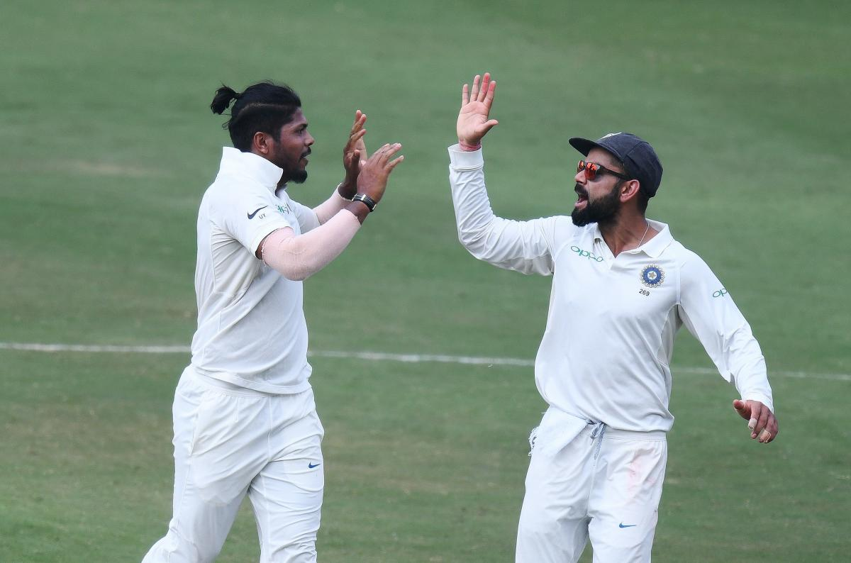Indian captain Virat Kohli and bowler Umesh Yadav celebrate the dismissal of Roston Chase during the third day's play of the second Test cricket match between India and West Indies at the Rajiv Gandhi International Cricket Stadium in Hyderabad on October