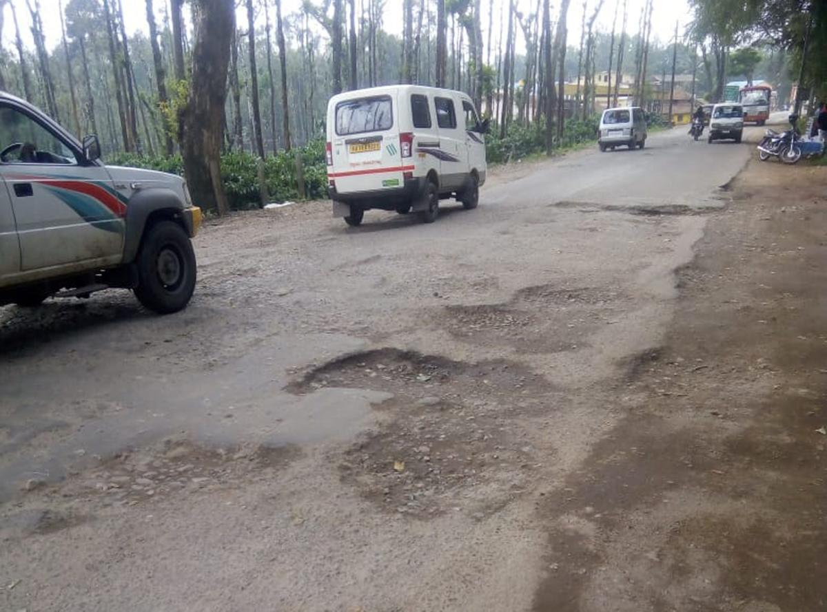 The pothole filled national highway at Handpost in Mudigere.