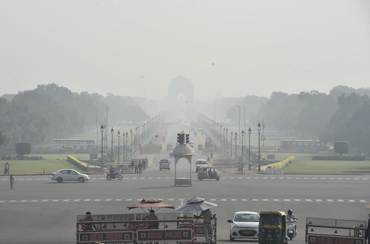 Vehicles ply on Rajpath as a thick smog engulfs India Gate in New Delhi. (PTI Photo)
