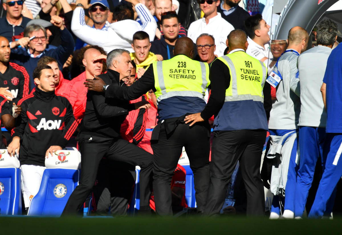 AGITATED Manchester United manager Jose Mourinho (left) is restrained by stewards after being irked by a member of Chelsea's backroom staff. REUTERS