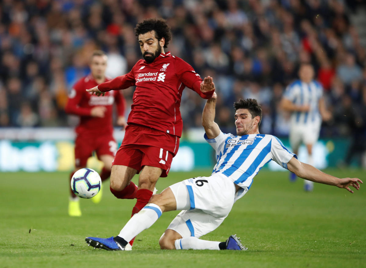 Huddersfield Town's Christopher Schindler attempts to tackle Liverpool's Mohamed Salah. Reuters