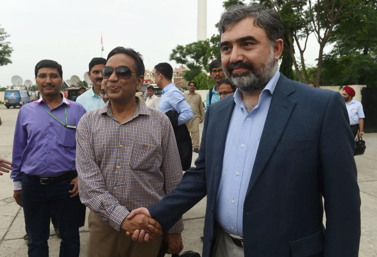 Pakistan's Commissioner for Indus Waters (PCIW) Syed Muhammad Mehar Ali Shah (R) shakes hands with Indian Indus Water Commissioner Pradeep Kumar Saxena (2L) on his arrival for a meeting to discuss Indus Waters Treaty and other issues, after crossing Wagah