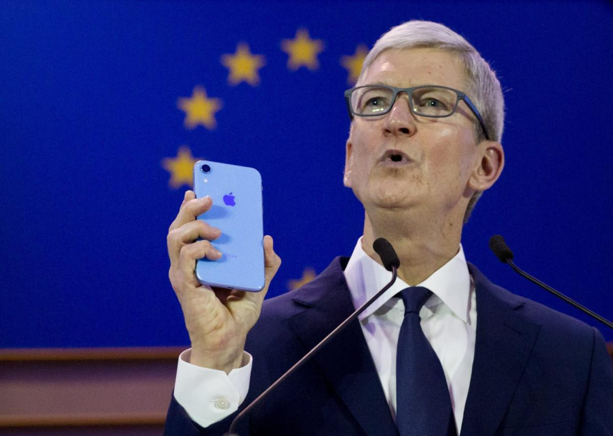 Apple CEO Tim Cook holds up an iPhone as he speaks during a data privacy conference at the European Parliament in Brussels on October 24, 2018. AP/PTI