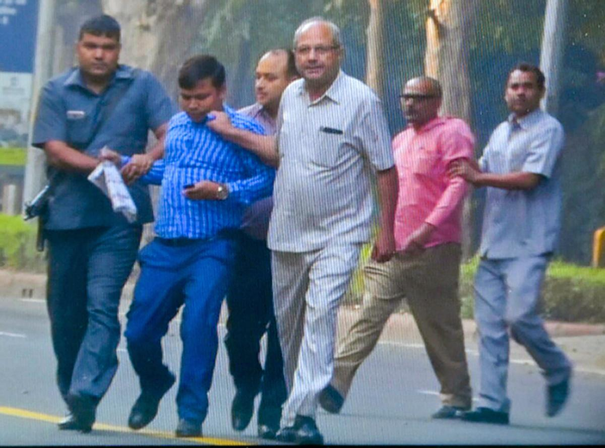 Security personnel detain two of the four people who were seen outside the residence of CBI director Alok Verma for questioning, on Thursday morning, in New Delhi, Thursday, Oct 25, 2018. (Video Grab/PTI Photo)