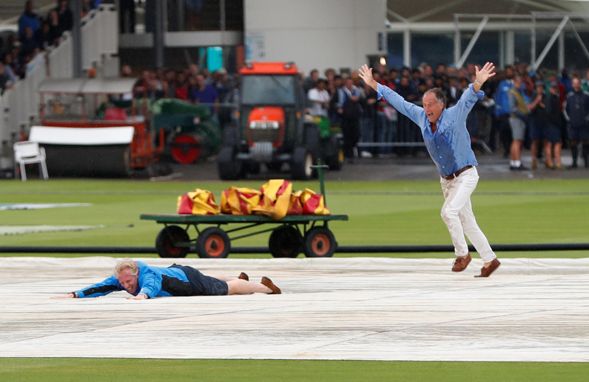 Spectators run onto the pitch and slide on the covers during rain delay on the opening day of the second Test at Lord's. Reuters