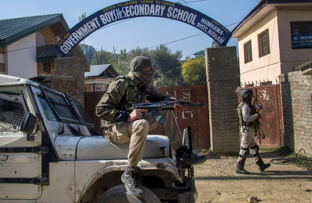 Security personnel stand guard at a polling station during the first phase of elections for urban local bodies, at Humhama in Budgam district of central Kashmir, Monday, October 8, 2018. (PTI File Photo/S Irfan)
