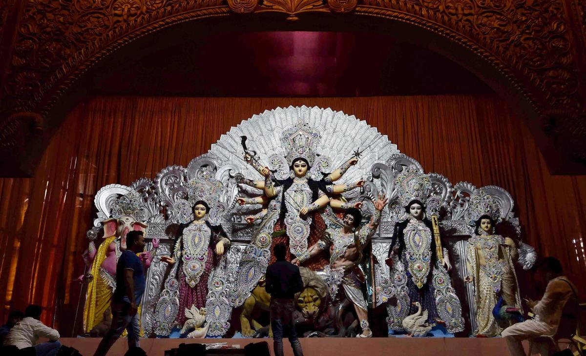 Artists give finishing touches to idols of deities at a Durga Puja pandal, in Kolkata, on Thursday. PTI